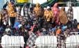 Migrantes esperam para desembarcar no porto de Catania, na ilha da Sicília, em 21 de março de 2017, após uma operação de resgate no mar Mediterrâneo