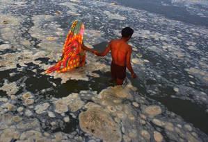 Devotos hindus se banham no poluído Rio Ganges Foto: SANJAY KANOJIA / AFP
