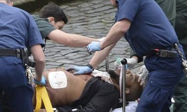 Suposto terrorista é socorrido por autoridades britânicas após atentado em Londres Foto: Stefan Rousseau / AP