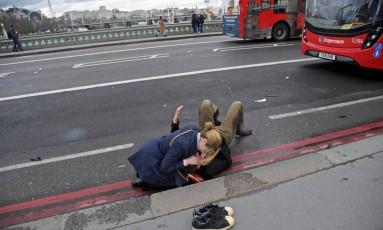 Mulher ajuda uma pessoa ferida na Ponte de Westminster após o atentado em Londres Foto: TOBY MELVILLE / REUTERS