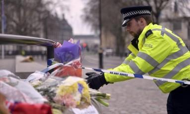 Policial deixa flores em homenagem a vítimas de ataque em Londres, em frente ao Palácio de Westminster Foto: HANNAH MCKAY / REUTERS