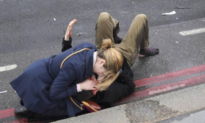 Uma mulher ajuda uma pessoa ferida após o incidente na ponte de Westminster em Londres. Foto: TOBY MELVILLE / REUTERS
