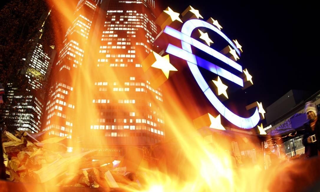 No movimento de ocupação em Frankfurt, manifestantes jogam fogo em escultura diante da sede do Banco Central Europeu. Protestos violentos contra a austeridade tomaram cidades europeias Foto: Michael Probst / AP