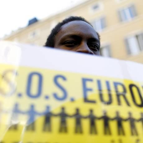 Migrante africano exibe cartaz pedindo socorro à Europa durante protesto em Roma Foto: YARA NARDI / Reuters