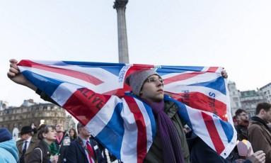 Homem segura bandeira do Reino Unido em vigília a vítimas do atentado terrorista que matou cinco pessoas e feriu outas 40 em Londres Foto: JOEL FORD / AFP