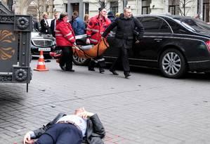 Corpo de Denis Voronenkov é visto estendido na rua, enquanto equipe de resgate carrega homem que matou o legislador russo, no centro de Kiev Foto: STRINGER / REUTERS