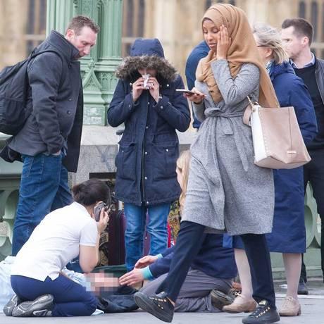 Mulher com hijab passa por vítima de atentado em Londres, na ponte de Westminster Foto: Jamie Lorriman