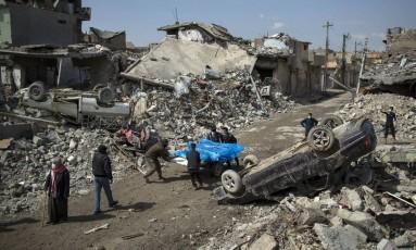 Residentes carregam corpos de pessoas mortas durante o embate entre as forças de segurança do Iraque e o Estado Islâmico, no lado Ocidental de Mosul, no Iraque Foto: Felipe Dana / AP