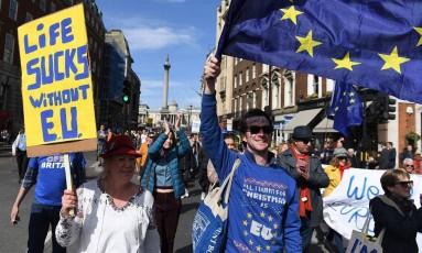 Uma mulher ergue um cartaz que diz 'A vida é uma droga sem a União Europeia', ao lado de um homem que balança a bandeira do bloco Foto: CHRIS J RATCLIFFE / AFP