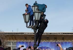 Policial escala um poste para alcançar manifestante Foto: SERGEI KARPUKHIN / REUTERS