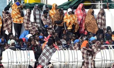 Imigrantes esperam o desembarque no porto de Catânia, na Sicília, Itália Foto: GIOVANNI ISOLINO / AFP