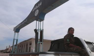 Uma combatente das forças sírias e curdas perto de um banner do Estado Islâmico, no aeroporto retomado neste domingo Foto: RODI SAID / REUTERS