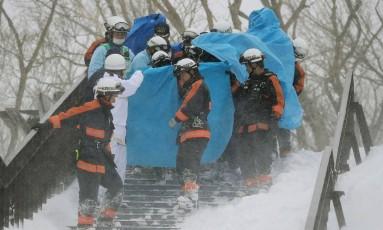 Bombeiros carregam um sobrevivente resgatado na avalanche que atingiu a cidade de Nasu Foto: JIJI PRESS / AFP