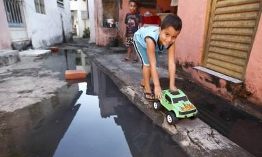 Menino brinca perto do esgoto no Rio de Janeiro Foto: Urbano Erbiste / Agência O Globo