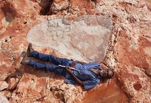 Aborígene se deita ao lado de pegada jurássica de 1,75 metro na Austrália Foto: HANDOUT / REUTERS
