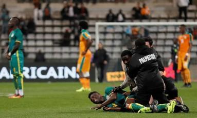 Torcedores saltam sobre jogador de Senegal em uma invasão de campo durante amistoso contra a Costa do Marfim em Paris Foto: THOMAS SAMSON / AFP