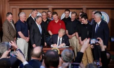 Trump assina a ordem ao lado de Scott Pruitt, diretor da EPA (terceiro à esquerda) e o vice-presidente Mike Pence (à direita) Foto: Pablo Martinez Monsivais/AP