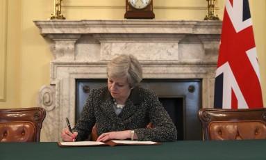Theresa May assina a carta comunicando à União Europeia a intenção de sair do bloco Foto: CHRISTOPHER FURLONG / AFP