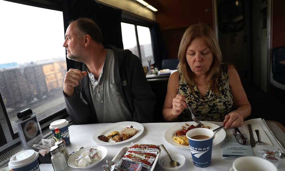 Bill Squier e Julie Blethen aproveitam o café da manhã servido pela Amtrak em passagem pela cidade de Denver, no Colorado, durante trajeto entre Chicago e Califórnia Foto: JOE RAEDLE / AFP