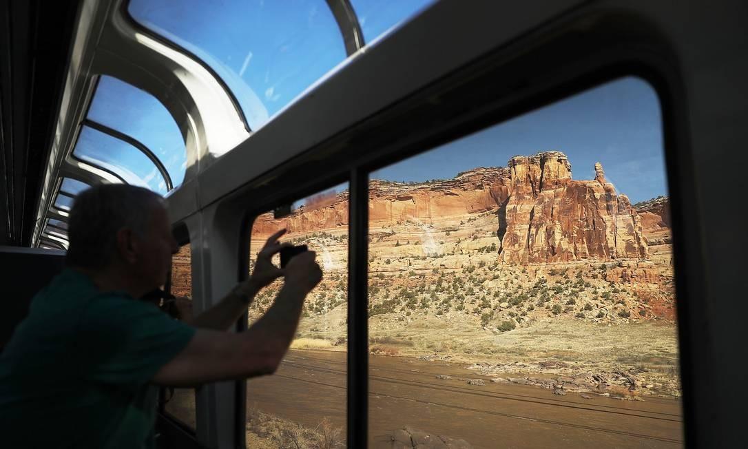 Passageiros fotografam o cenário desértico do estado de Utah durante viagem da linha Zephyr Foto: JOE RAEDLE / AFP