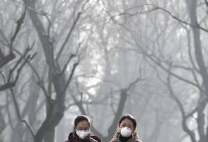 Chinesas usam máscaras para se proteger da poluição no parque Ritan, em Pequim Foto: Andy Wong / AP