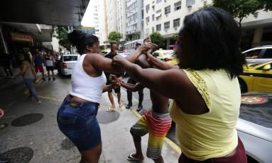 Mãe (de branco) se descontrola em frente à delegacia de Copacabana e bate no filho levado pela polícia por envolvimento com o tráfico. Na foto, ela é contida pela avó da criança Foto: Pablo Jacob / Agência O Globo