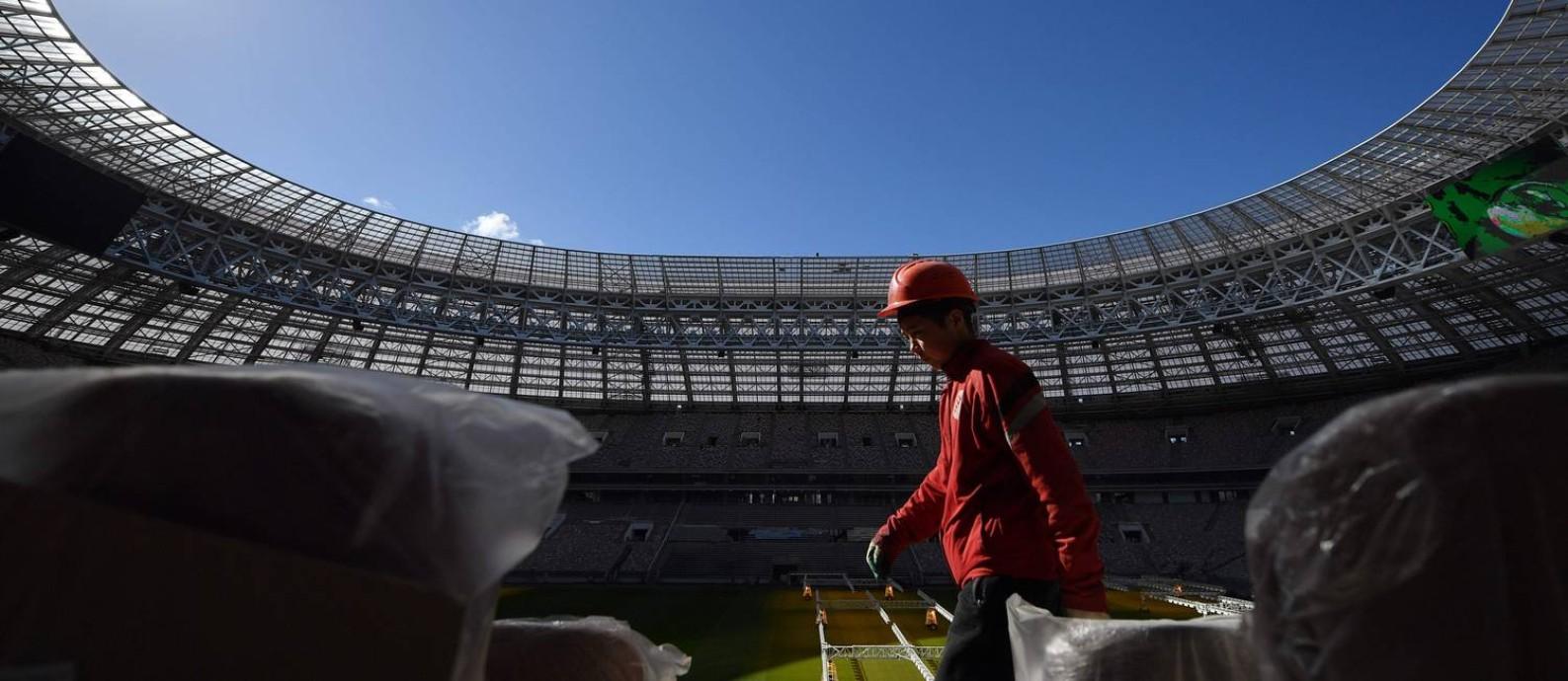 Operário caminha pelo estádio de Luzhniki, um dos palcos que receberá jogos da Copa de 2018 em Moscou Foto: NATALIA KOLESNIKOVA / AFP