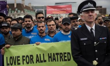 Um policial e muçulmanos britânicos fazem parte de uma vigília na Ponte de Westminster em homenagem às vítimas do atentado que se sucedeu semana passada em Londres Foto: OLI SCARFF / AFP