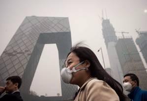 Mulher usa máscara de proteção em Pequim Foto: NICOLAS ASFOURI/AFP/20-3-2017