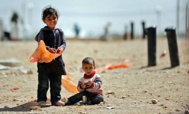 Pequenos refugiados sírios olham para a câmera em campo que abriga 80 mil pessoas na fronteira entre Jordânia e Síria Foto: THOMAS COEX / AFP