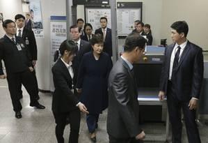 Park (ao centro, conduzida por agentes) deixa o local onde prestou depoimento antes de a Justiça aprovar sua detenção Foto: Ahn Young-joon / AP