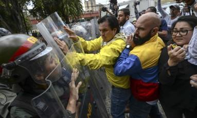 Os deputados venezuelanos de oposição Carlos Paparoni e Carloz Bozo empurram os escudos da Guarda Nacional durante um protesto em frente à Suprema Corte, em Caracas Foto: JUAN BARRETO / AFP