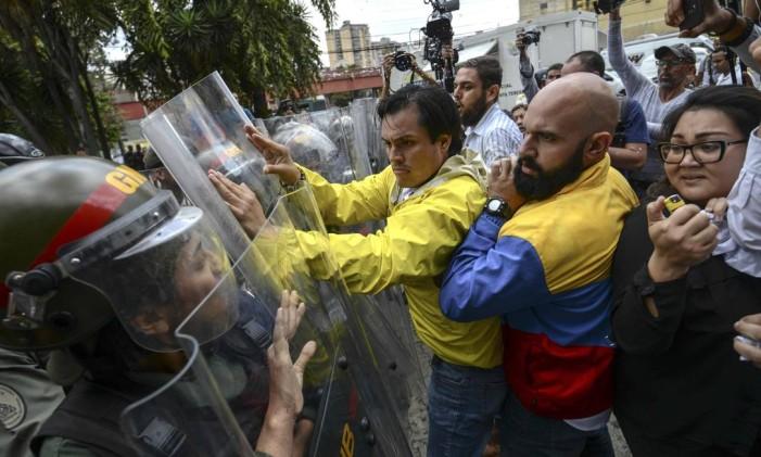 Deputados de oposição venezuelanos Carlos Paparoni e Marco Bozo brigam com a Guarda Nacional durante protesto Foto: JUAN BARRETO / AFP