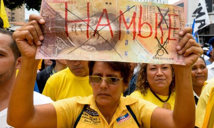 """Uma mulher segura um cartaz escrito """"fome"""", na Venezuela Foto: FEDERICO PARRA / AFP"""