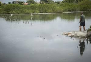 Antes e depois. Na imagem acima, pescador joga tarrafa à frente de um pequeno cais de madeira que estava aterrado em fevereiro Foto: Analice Paron / Agência O Globo
