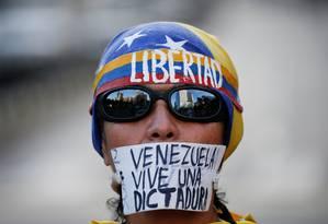 Manifestante tapa boca com mensagem dizendo que a Venezuela 'vive uma ditadura' Foto: CARLOS GARCIA RAWLINS / REUTERS
