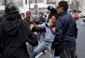 Campo de guerra. Usando um capacete, apoiador do governo enforca um manifestante: protesto em Caracas, do lado do fora do Supremo, foi marcado por violência Foto: MARCO BELLO/REUTERS