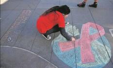 Mulher da Califórnia, nos EUA, desenha o símbolo da luta contra a Aids