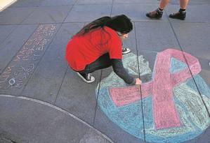 Mulher da Califórnia, nos EUA, desenha o símbolo da luta contra a Aids Foto: Justin Sullivan/AFP