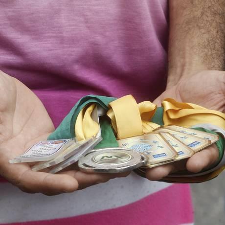Um dos irmãos de Maria Eduarda mostra as medalhas que a adolescente ganhou em competições colegiais: prática esportiva garantiu a ela uma bolsa em escola particular de Jacarepaguá Foto: Antonio Scorza / Agência O Globo