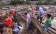 Equipes de resgate procuram vítimas de deslizamento de terra sob escombros
