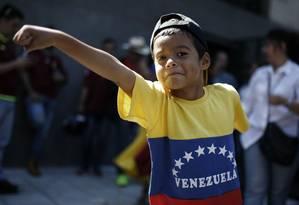 Menino veste camisa com cores da bandeira venezuelana em manifestação contra Maduro na frente do Ministério das Relações Exteriores em Buenos Aires, na Argentina Foto: Agustin Marcarian / AP