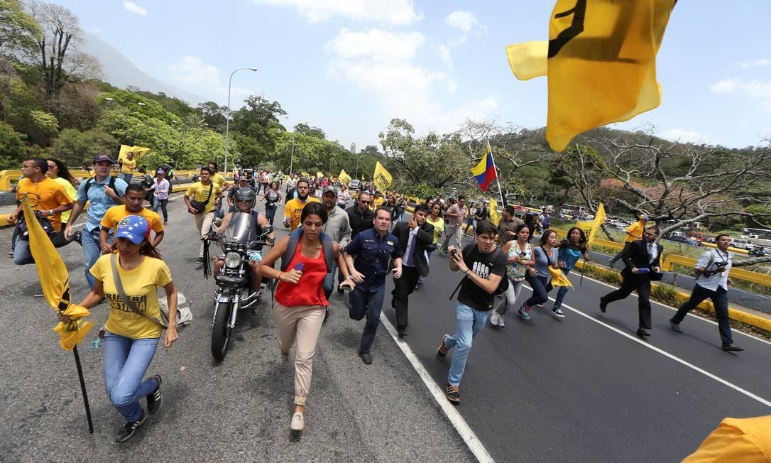 Manifestantes correm enquanto bloqueiam uma avenida durante um protesto contra o presidente da Venezuela, Nicolás Maduro Foto: CARLOS GARCIA RAWLINS / REUTERS