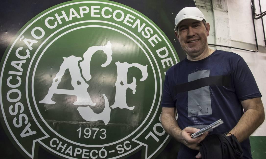 O jornalissta Rafael Henzel em frente ao escudo da Chapecoense, na Arena Condá Foto: NELSON ALMEIDA / Agência O Globo