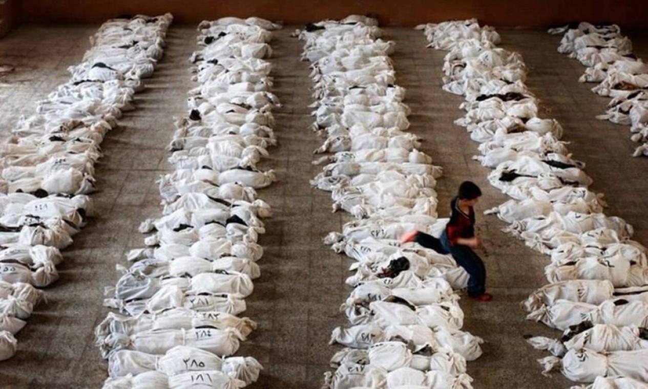 Menino passa por cima de corpos de crianças mortas em ataque químico em Ghouta, na Síria, em 2013: ataque deixou centenas de mortos. Número é incerto até hoje Foto: Reprodução