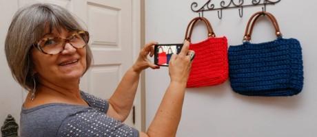 O smartphone ajuda Regina Braga Ribeiro a criar, produzir e vender as bolsas de crochê que produz Foto: Marcelo de Jesus