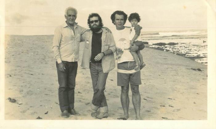 SC - Gramiro de Matos (carregando o filho no colo), com seu pai (à extrema esquerda) e Mario Cravo Neto (ao lado), na praia de Amaralina, em Salvador Foto: Fagner / Acervo pessoal