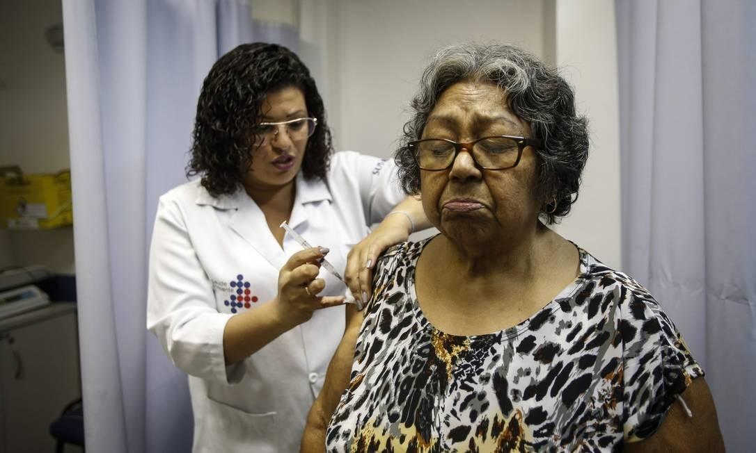 Já imunizada contra a febre amarela, Maria Edvirgns toma vacinas para combater hepatite B e contra tétano e difteria em um posto de saúde no Centro do Rio Foto: / Alexandre Cassiano