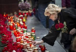 Mulher deixa flores em memorial a vítimas de ataque terrorista que matou 14 pessoas em São Petersburgo, na Rússia Foto: Alexander Zemlianichenko / AP