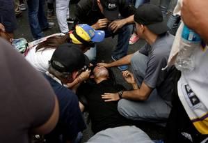 Manifestante sofre com efeitos de gás lacrimogêneo durante protesto em Caracas Foto: CARLOS GARCIA RAWLINS / REUTERS